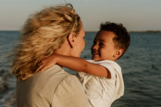 Grandmother carrying grandson while standing by sea during sunset