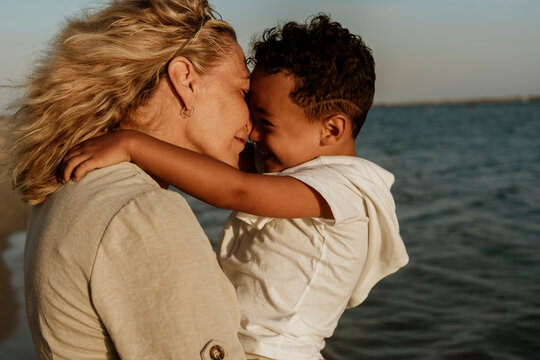 Grandmother nuzzling grandson while carrying him at beach during sunset