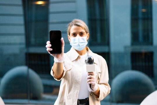 Female journalist wearing mask showing smart phone while standing in city