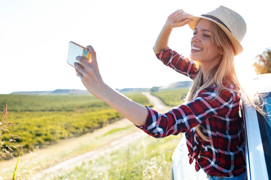Young woman taking selfie through mobile phone while leaning out of car window
