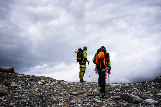 Male friends hiking on mountain against cloudy sky at Stelvio National Park, Italy
