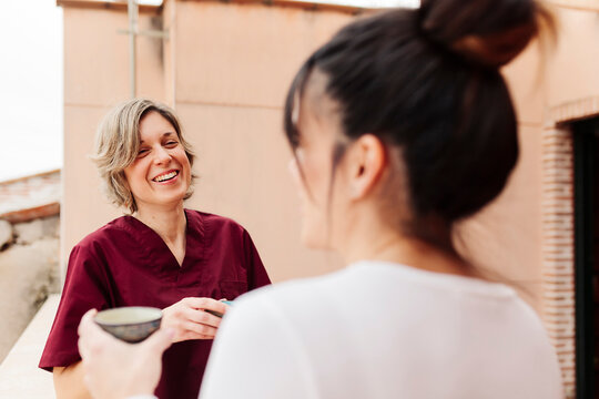 Smiling physiotherapist talking with woman while standing at rooftop