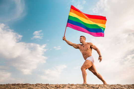 Shirtless young man holding rainbow flag walking at beach against sky