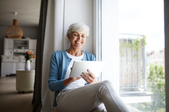 Smiling senior female using digital tablet while sitting on window at home