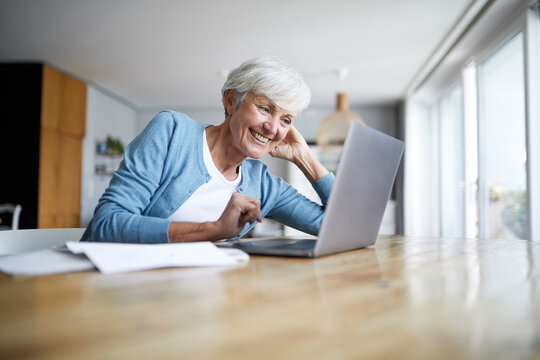Smiling senior woman with hands behind head looking at laptop