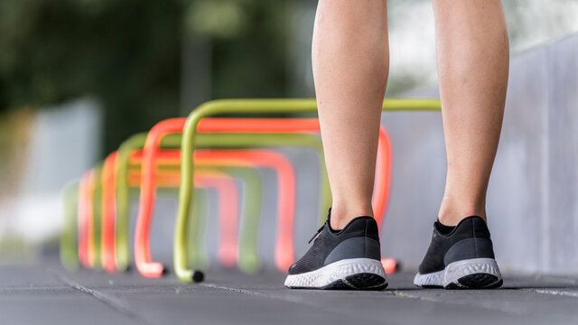 Legs of young woman standing by small hurdle