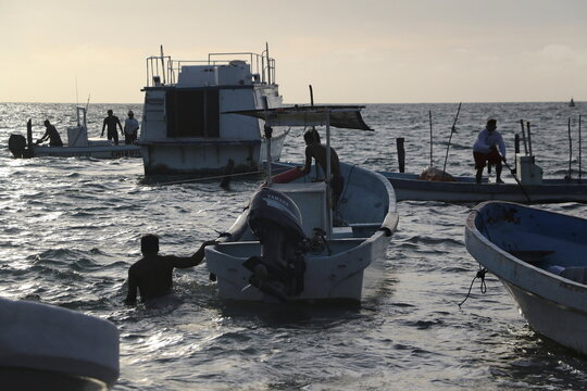 Fishermen prepare to take their boats off the water as Hurricane Zeta approaches Cancun