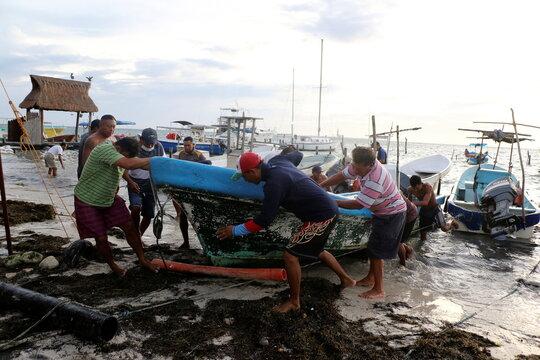Fishermen take a boat off the water as Hurricane Zeta approaches Cancun