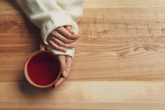 Woman holding cup of tea at wooden table, top view. Space for text