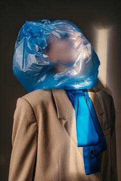 Stylish woman suffocating under plastic bag