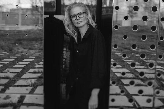 Woman among steel mirror panels
