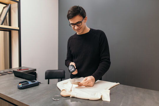 Content man with scanner working in clothing store
