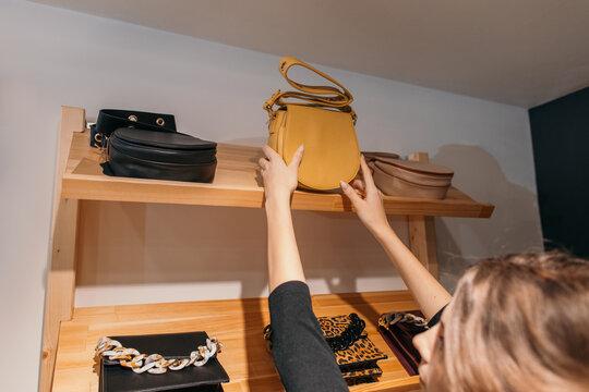 Woman taking handbag from shelf in store