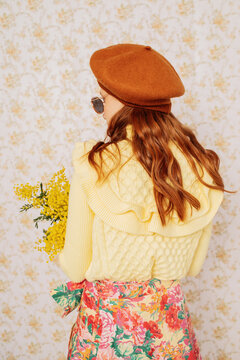 Female model with flowers against floral wall