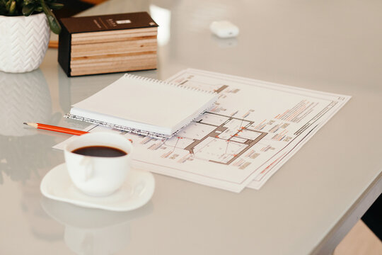 Coffee and notebook near drafts on table