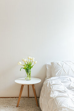 White bedroom with tulips on side table