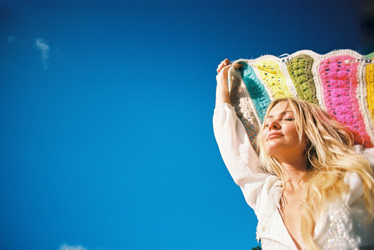 Blonde young woman with blue sky and rainbow colors