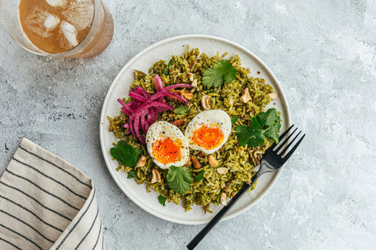 Vegetarian rice dish with soft boiled egg and pickled purple onions