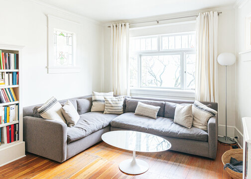 Cozy living room with sofa, cushions, window and coffee table