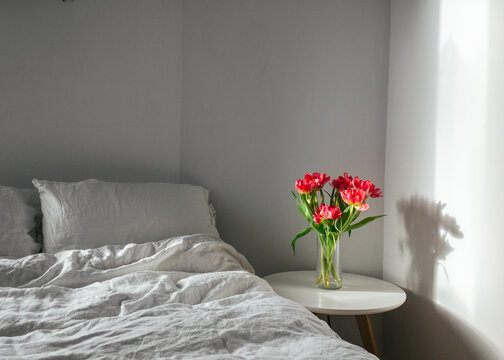 Bbedroom interior with bed, coffee table and flowers in vase