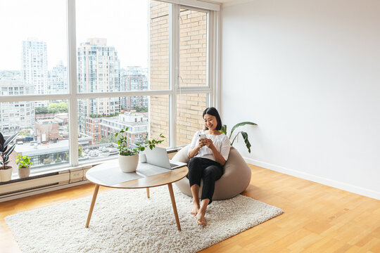 Female using cell phone in minimalist apartment