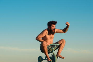 Excited young male riding a small bicycle and gesturing happiness. Funny crazy man riding a bike....