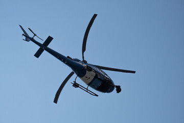helicopter flying in the solid blue colored sky