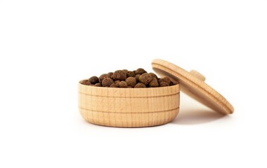 Fototapeta a dried aromatic allspice pepper fruit in wooden bowl isolated on white background, the concept of kitchenware made from natural materials obraz