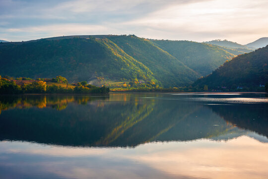 gilau lake of cluj country in evening light. beautiful landscape of romania in autumn. reflection on the calm water surface. trees in colorful foliage. sunny weather
