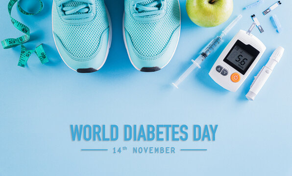 Top view of diabetes tester set with sport shoes, measuring tape and  green apple on bright blue pastel background. World diabetes day concept.