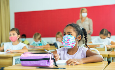 Diligent african tween girl in protective mask studying in school with classmates. New life reality...
