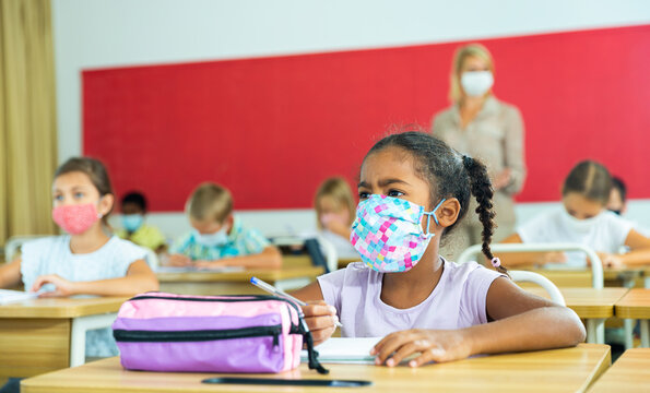 Diligent african tween girl in protective mask studying in school with classmates. New life reality in coronavirus pandemic