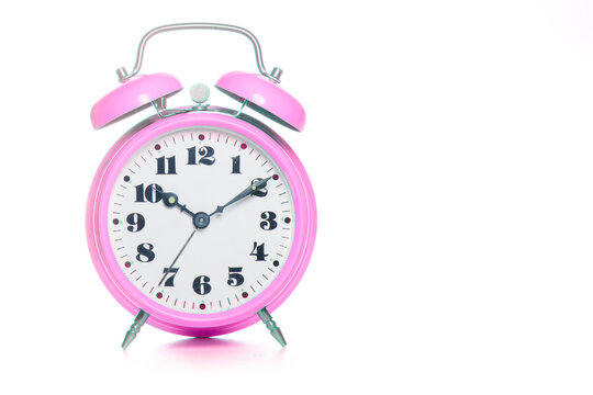 Classic pink table alarm clock on a white background