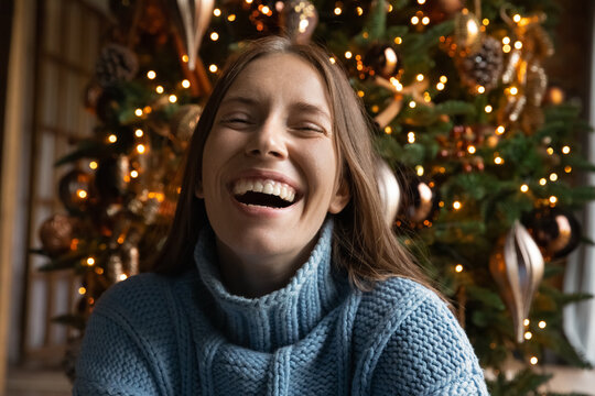 Close up portrait of overjoyed young Caucasian woman have fun laugh and joke enjoying Christmas winter holidays at home. Excited millennial female feel playful positive and joyful, celebrate New Year.
