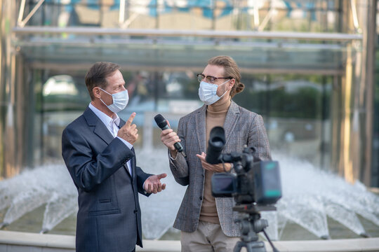 Fair-haired male journalist interviewing mature male in front of camera, both wearing masks