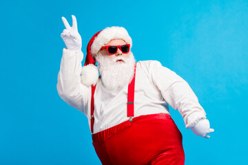 Photo of cool funky overweight santa claus with big belly beard dance x-mas christmas discotheque wear headwear suspenders overalls sunglass isolated over blue color background