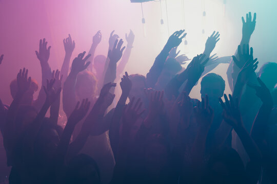 Photo of big group gather concert many funny people raise arms neon bright spotlight modern club indoors