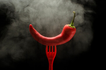 Closeup of steam, red fork and red hot chili pepper on it against black background