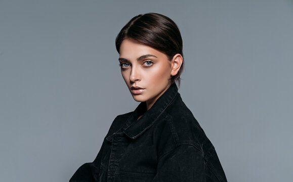 Studio shoot of young sexy brunette woman wear black denim jacket isolated on grey background