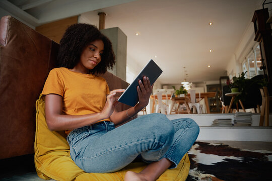 Young woman sitting at home on floor with digital tablet