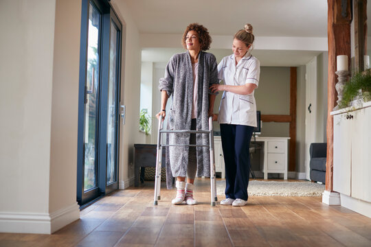 Mature Woman In Dressing Gown Using Walking Frame Being Helped By Female Nurse