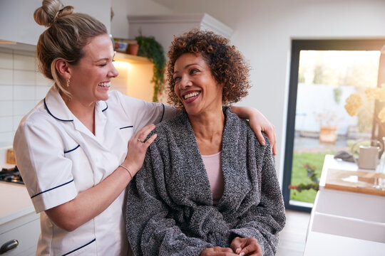 Mature Woman In Dressing Gown Talking With Female Nurse In Kitchen At Home