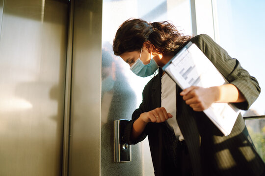 Business woman  in medical face mask uses an elbow to press the elevator button to prevent the spread of the Covid - 19. Office manadger back at work in office after quarantine.