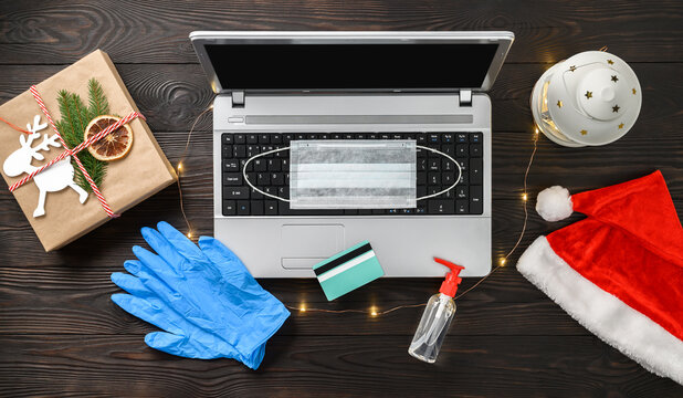 Christmas online shopping theme during Coronavirus. Laptop, credit card, gift box, Santa hat, medical mask, antiseptic and gloves on dark wooden background. Top view, flat lay.