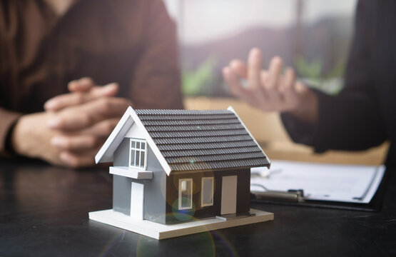 Home buyers meet and negotiate with real estate agents about renting or buying a home in the office.