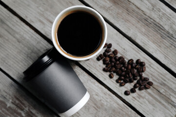 top view hot Americano coffee or black coffee in a gray paper cup and coffee beans placed on a wooden table.