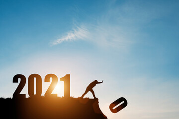Man push number zero down the cliff where has the number 2021 with blue sky and sunrise. It is...