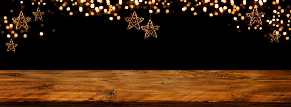 Golden Christmas stars with festive bokeh lights in front of illuminated rustic wooden table. Background for christmas and new years concepts. Space for text and design.
