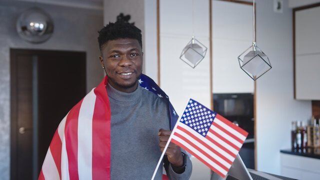Black man with USA flag over the shoulders and small one in hand. High quality photo