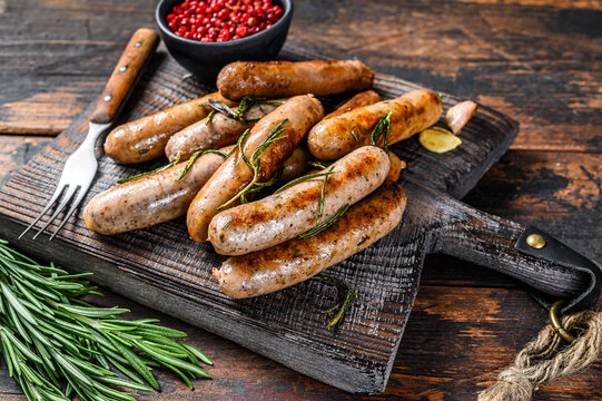Grilling bavarian sausages on a cutting board. Dark wooden background. Top view